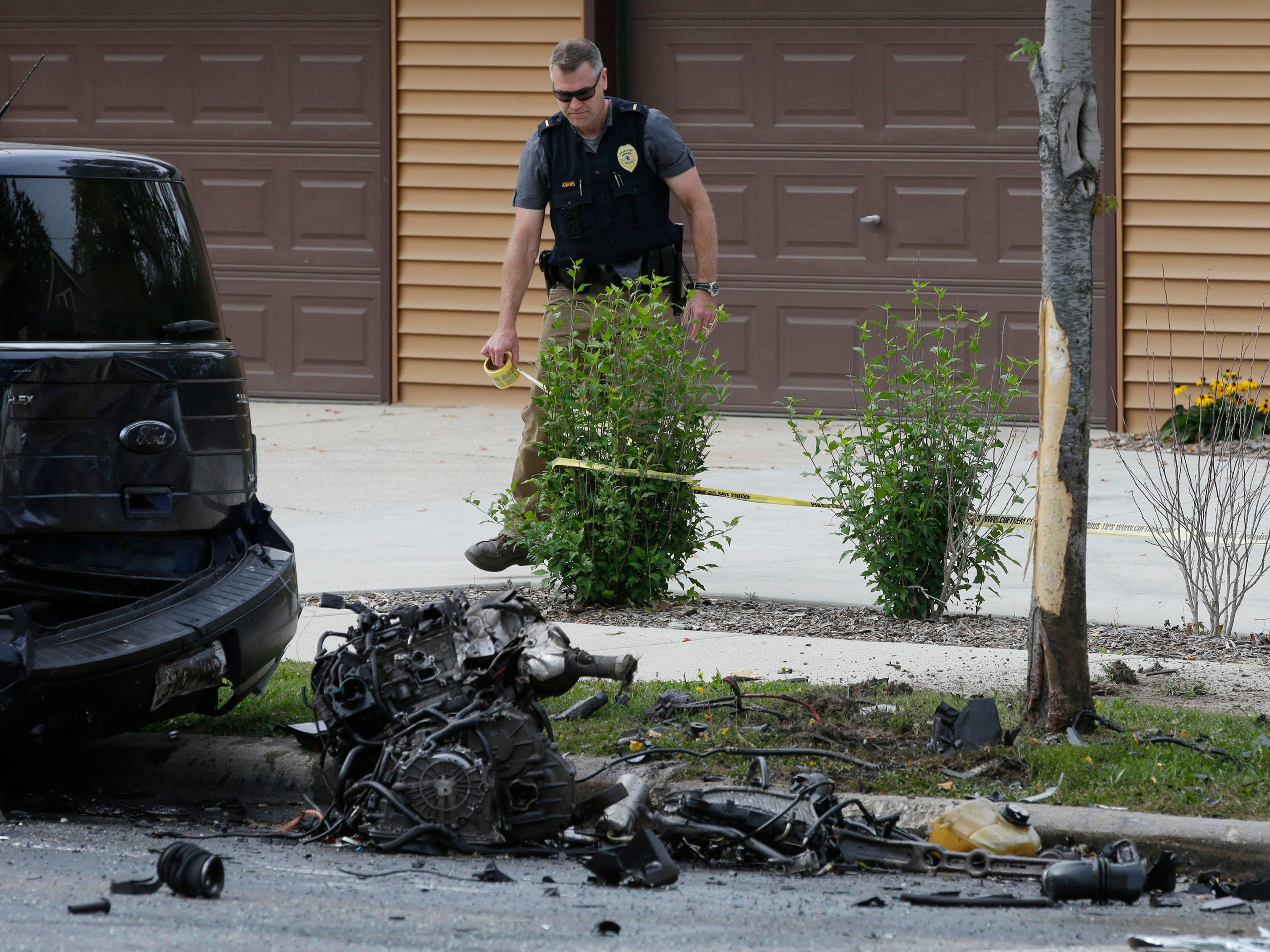 Sheboygan police wrap police tape at the scene of a 2-car crash on Pennsylvania Avenue between 14th and 15th streets, Tuesday, September 18, 2018, in Sheboygan, Wis. A third parked car was also struck. Two people died as a result of the crash.