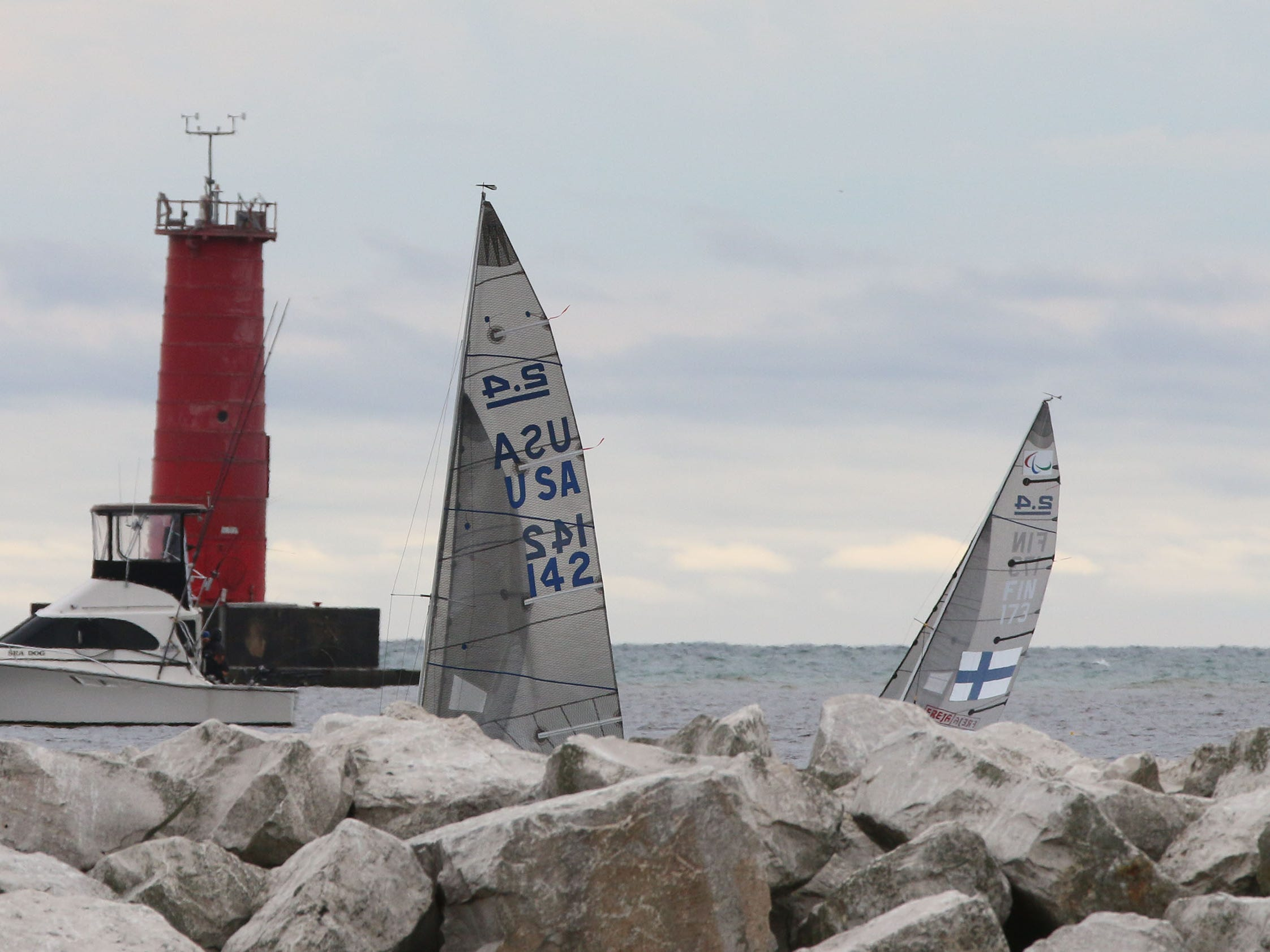 A USA sailor, left, and a Finland sailor heads out to sea to compete in the Para World Sailing Championships, Tuesday, September 18, 2018, in Sheboygan, Wis.