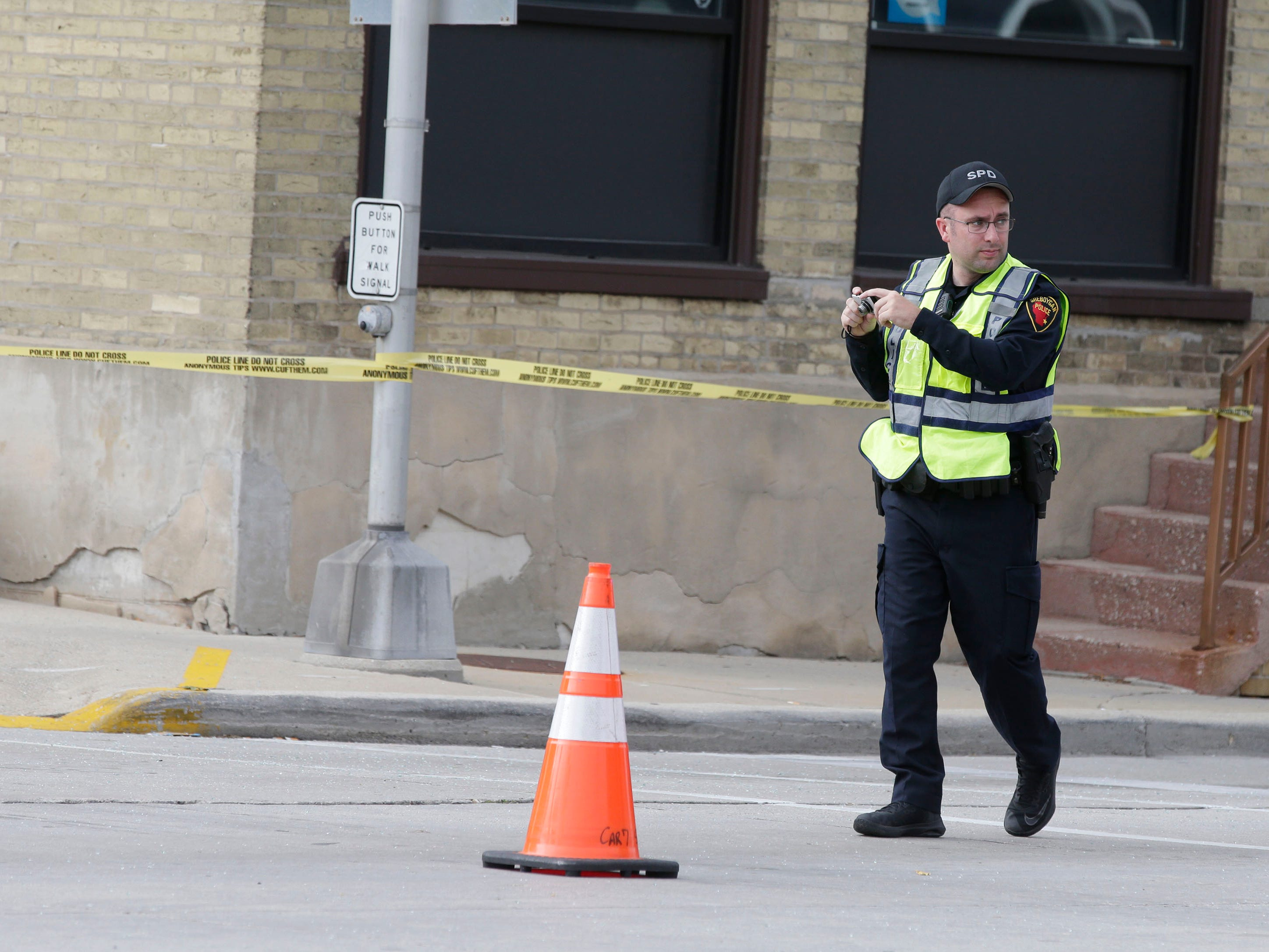 A Sheboygan police officer looks before taking photos at the scene of a 2-car crash on Pennsylvania Avenue between 14th and 15th streets, Tuesday, September 18, 2018, in Sheboygan, Wis. A third parked car was also struck. Two people died as a result of the crash.