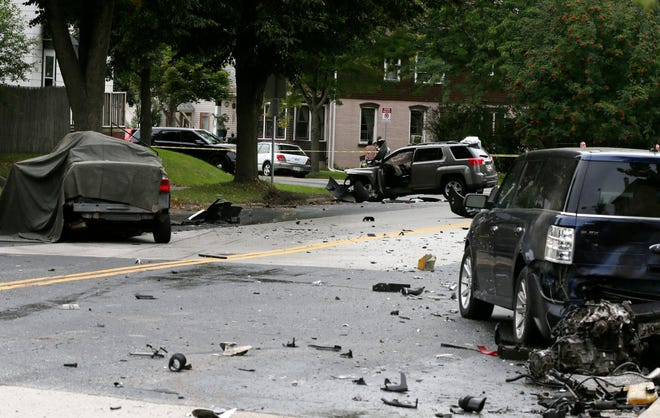 Debris is strewn at the scene of a 2-car crash on Pennsylvania Avenue between 14th and 15th streets, Tuesday, September 18, 2018, in Sheboygan, Wis. A third parked car was also struck.