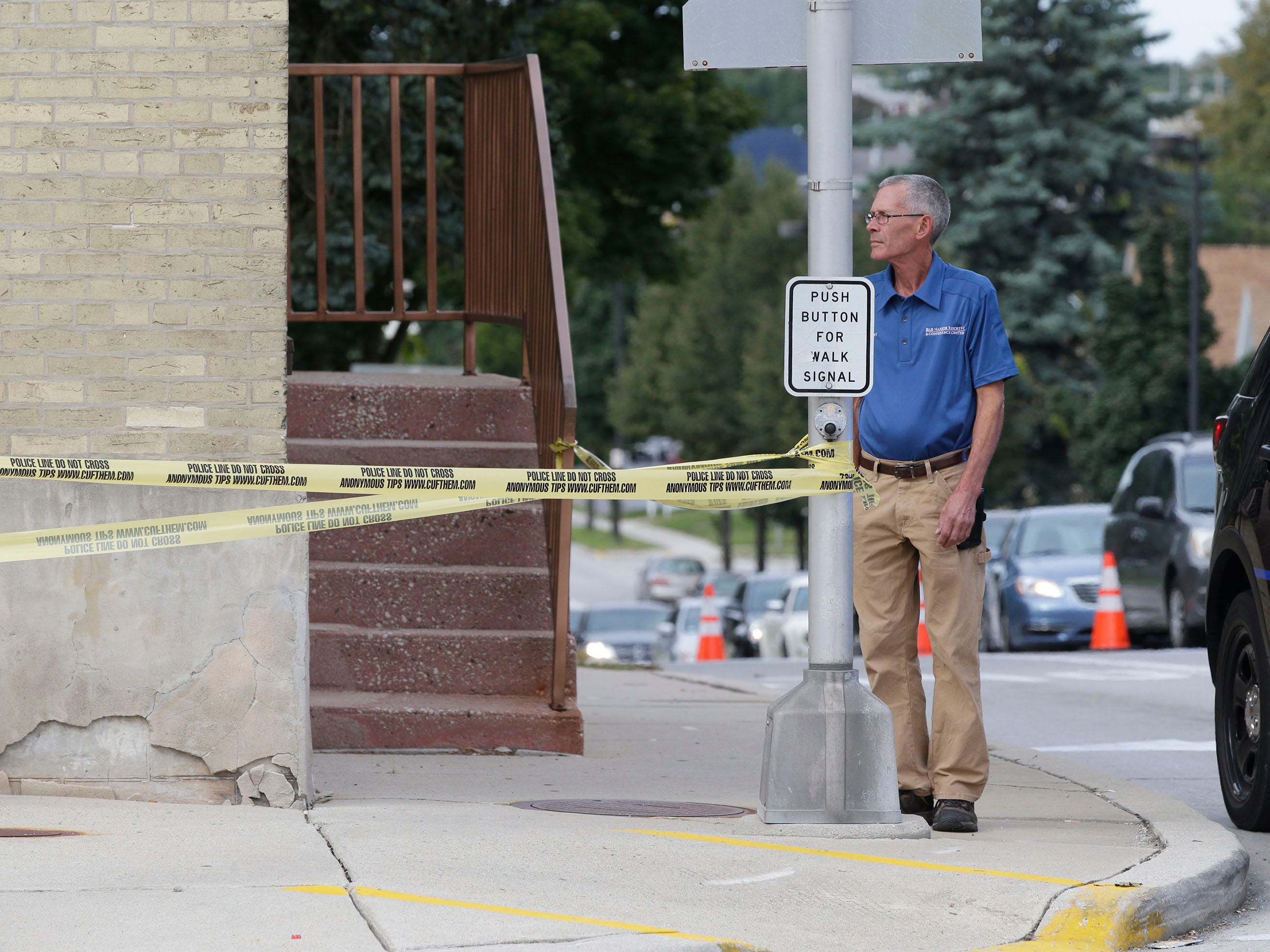 A bystander looks over the scene of a 2-car crash on Pennsylvania Avenue between 14th and 15th streets, Tuesday, September 18, 2018, in Sheboygan, Wis. A third parked car was also struck. Two people died as a result of the crash.