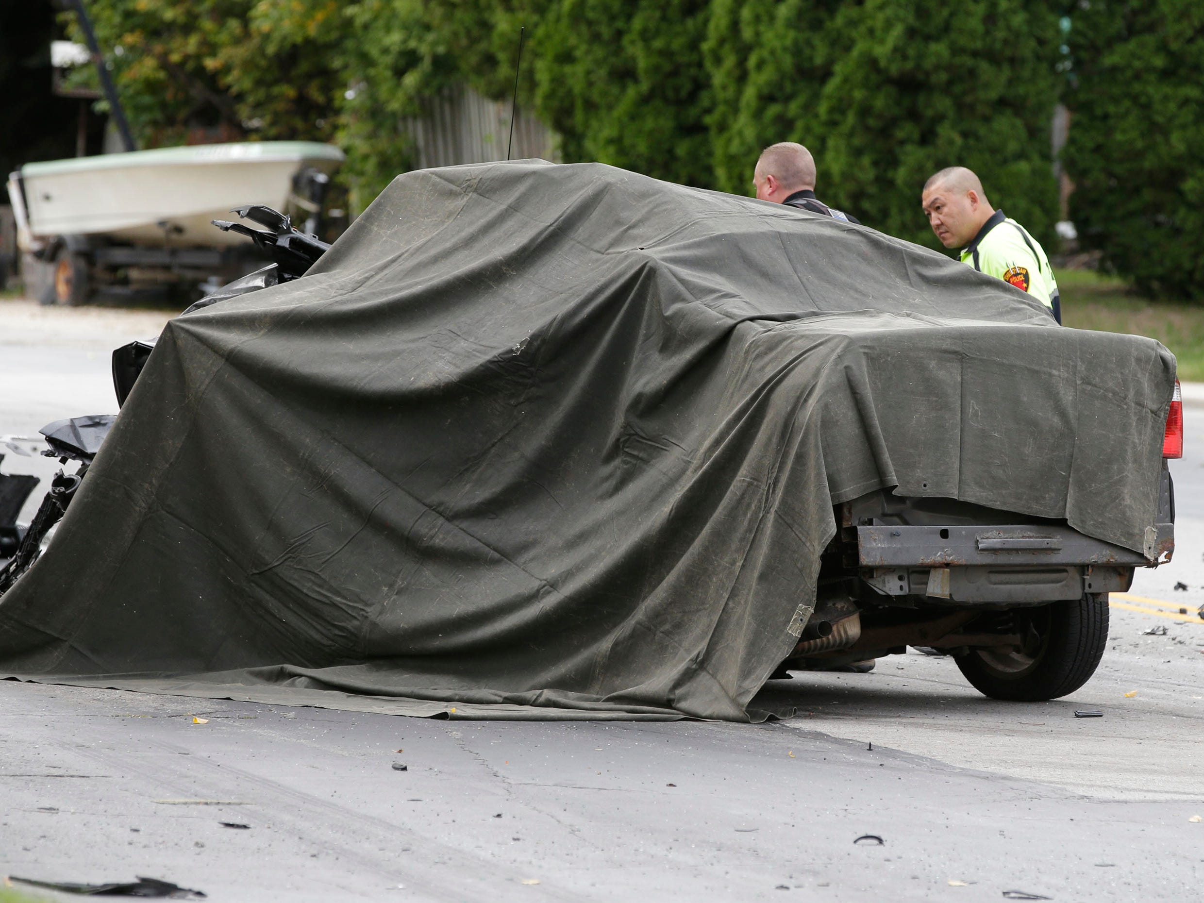 A tarp covers a vehicle at the scene of a 2-car crash on Pennsylvania Avenue between 14th and 15th streets, Tuesday, September 18, 2018, in Sheboygan, Wis. A third parked car was also struck. Two people died as a result of the crash.
