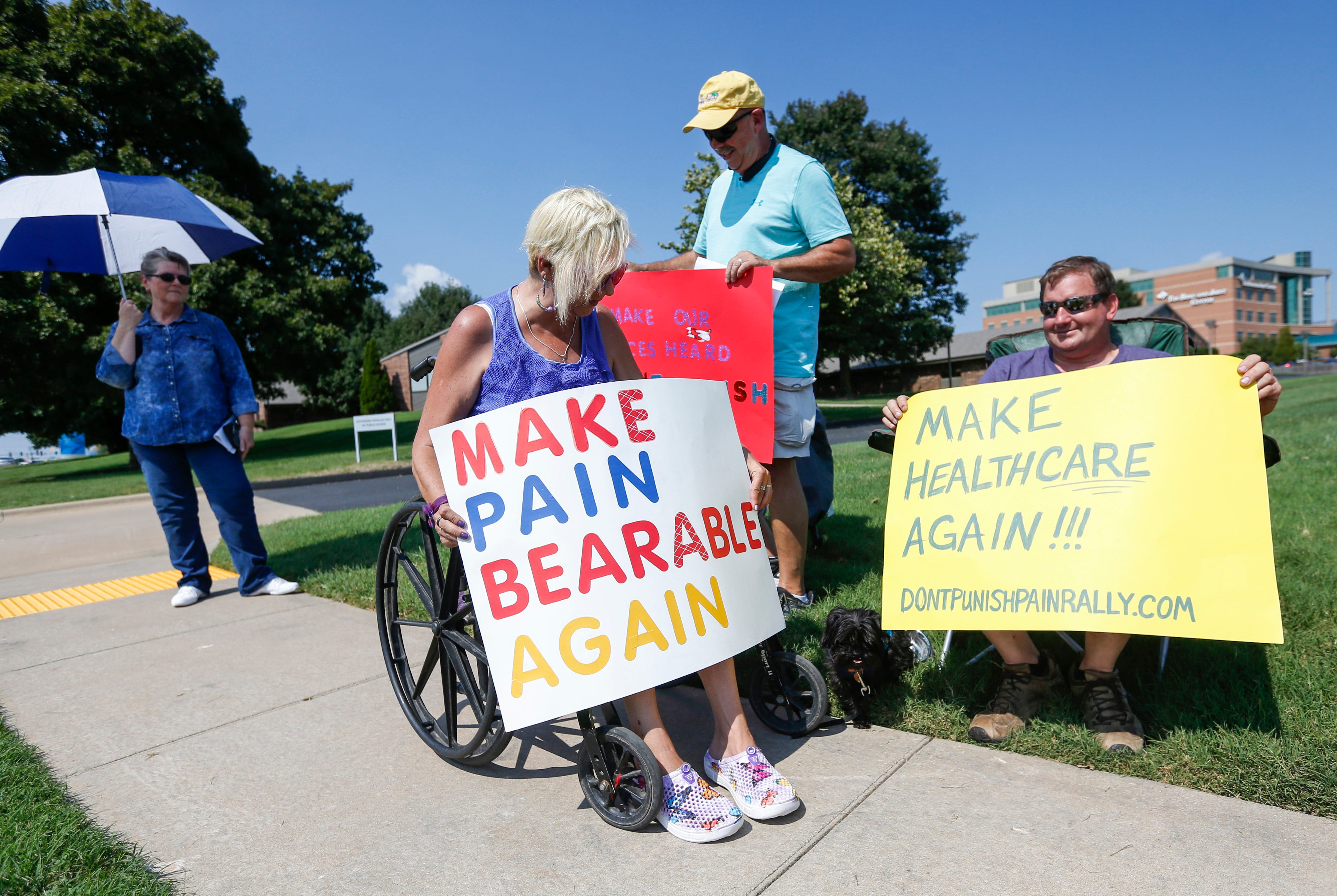 From right, Daniel Sweatt, Ray Oldham, and Kathleen Sweatt hold ups signs during a rally outside of Cox South Hospital on Tuesday, Sep. 18, 2018. Chronic Pain patients held the rally because they believe they are being punished by recent CDC guidelines that discourage doctors from writing prescriptions for pain medication.