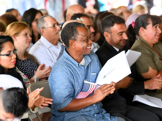 Khmis Mohamed Hassan smiles broadly as he joins fellow petitioners in applauding after Earnest Holly sang the national anthem during a naturalization ceremony held at the Frontier Culture Museum on Tuesday, Sept. 18. 2018.