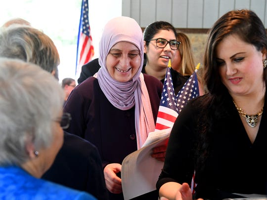One new American citizen smiles after coming off the stage with her certificate of naturalization in hand during a naturalization ceremony held at the Frontier Culture Museum on Tuesday, Sept. 18. 2018.