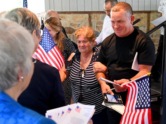 Newly naturalized American citizens receive small gifts, such as an American flag, after crossing the stage and receiving their certificates of naturalization during a naturalization ceremony held at the Frontier Culture Museum on Tuesday, Sept. 18. 2018.