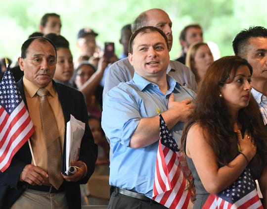 Akaki Alexandria says the pledge of allegiance at the end of the naturalization ceremony at the Frontier Culture Museum Sept. 18.