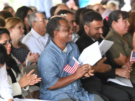A group of newly naturalized citizens clap at the ceremony at the Frontier Culture Museum Sept. 18.