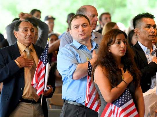 A newly naturalized American citizen, Akaki Alexandria has hand over his heart and says the pledge of allegiance at the end of the during a naturalization ceremony held at the Frontier Culture Museum on Tuesday, Sept. 18. 2018.