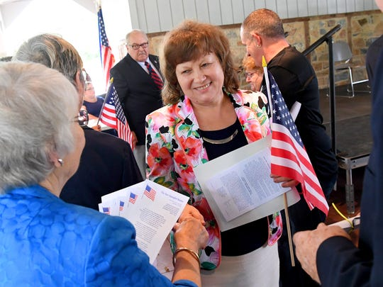 Certificate of naturalization in hand, a new American citizen smiles as she receives an American flag and other small gifts during a naturalization ceremony held at the Frontier Culture Museum on Tuesday, Sept. 18. 2018.