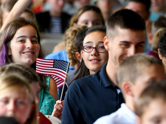 Some of the students attending the event wave flags at the naturalization ceremony held at the Frontier Culture Museum on Tuesday, Sept. 18. 2018.