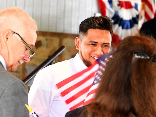 Miguel Angel Castaneda smiles after stepping off stage with his certificate of naturalization in hand and is gifted with an American flag during a naturalization ceremony held at the Frontier Culture Museum on Tuesday, Sept. 18. 2018.