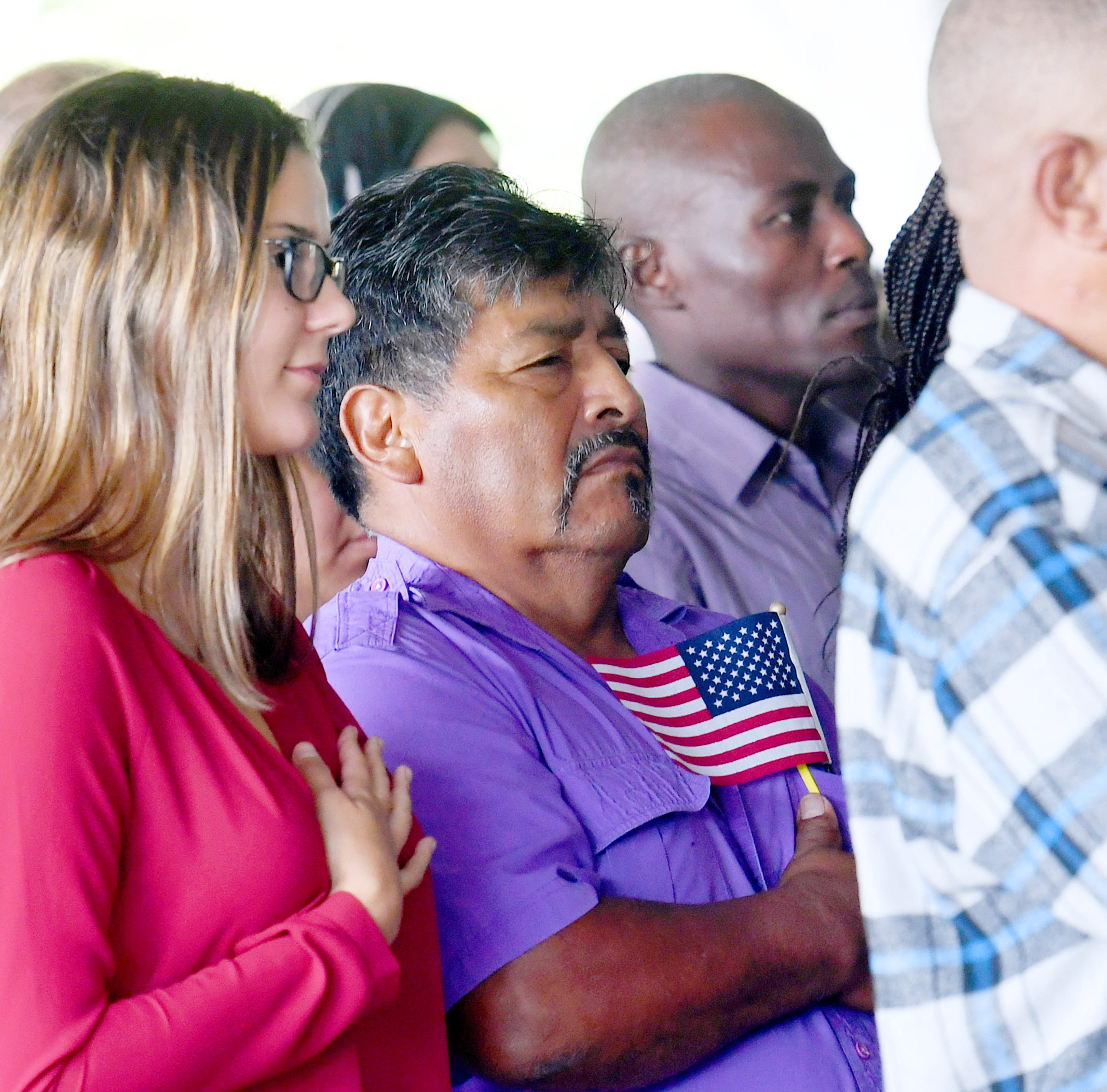 One petitioner for citizenship holds a small American flag over his heart as the national anthem is sung during a naturalization ceremony held at the Frontier Culture Museum on Tuesday, Sept. 18. 2018.