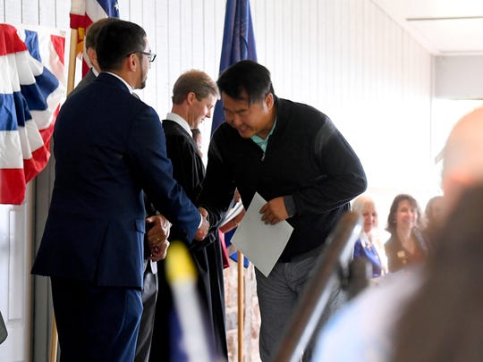 Dong Il Kim, originally of South Korea, bows one-by-one to each person on stage after he receives his certificate of naturalization during a naturalization ceremony held at the Frontier Culture Museum on Tuesday, Sept. 18. 2018.