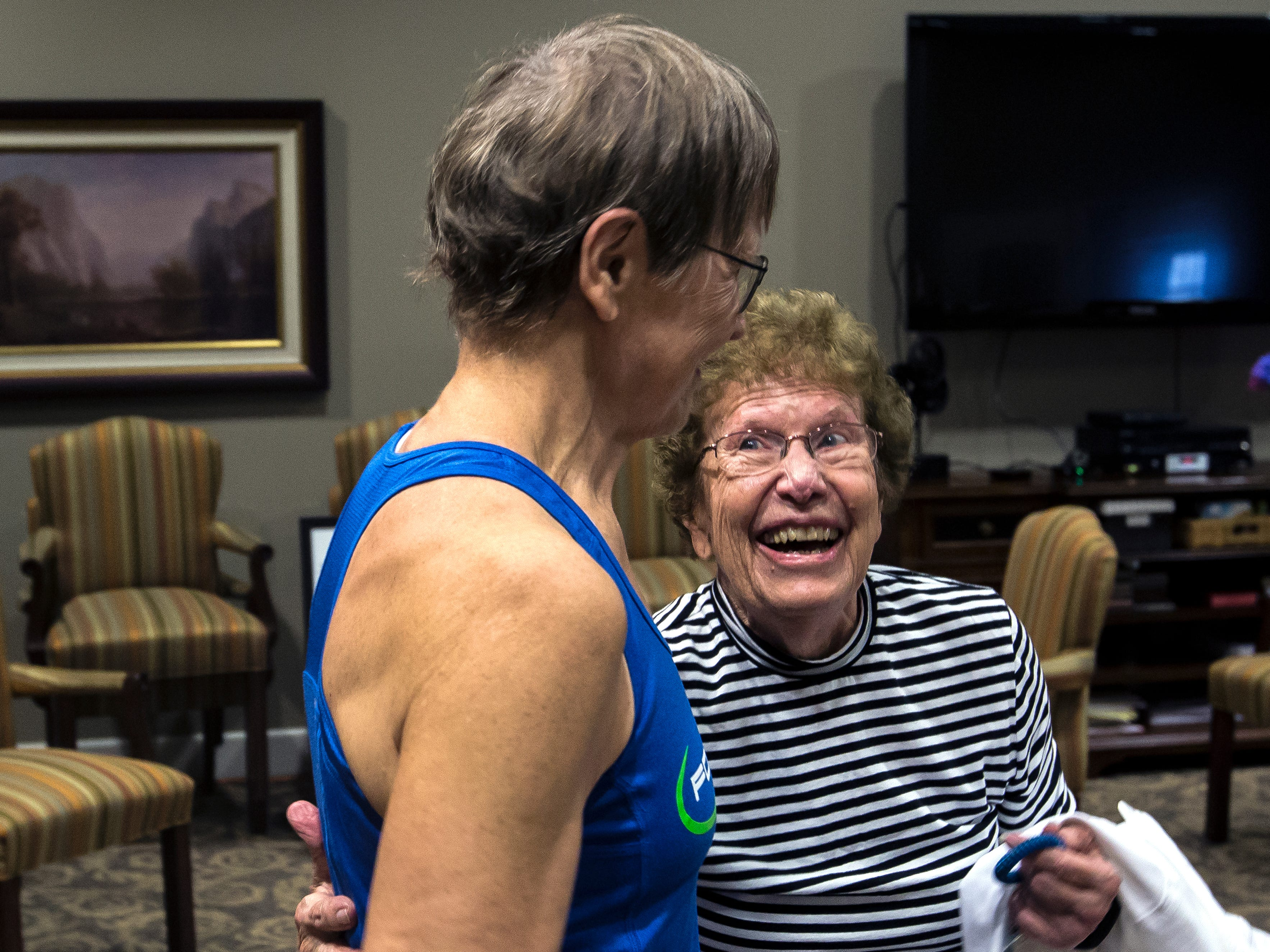 A participant hugs Betty Lou Sweeney after she led a class for elderly residents of the Brookdale assisted living facility in Stevens Point, Wis., Tuesday, Sept. 18, 2018. Sweeney volunteers to run the class on a weekly basis.