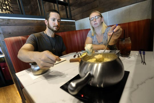 Danielle and Michael Jones dip in to a cheese fondue at The Melting Pot at The Fountains at Farah.