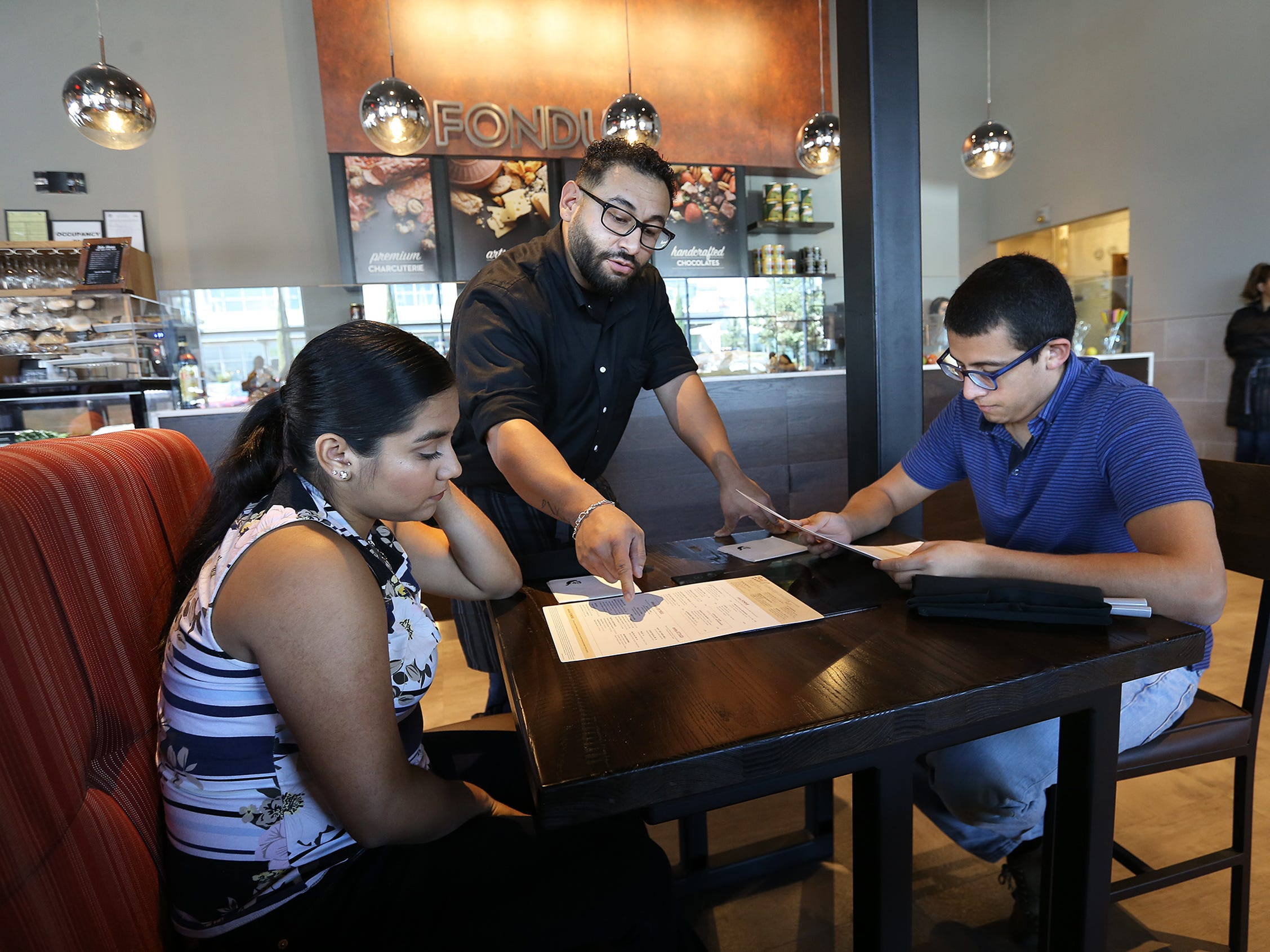 The Melting Pot server Alexander Salas walks customers Vanessa Maldonado and Joshua Lopez through the menu options at the newly opened fondue restaurant at The Fountains at Farah Tuesday.