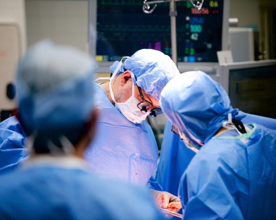 Dr. Aleksandr Reznichenko, center, takes part in a liver transplant surgery last year at the University of Cincinnati Medical Center.