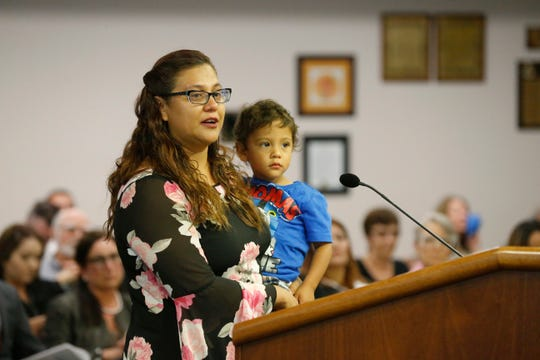 Veronica Ramos holds her son as she addresses the El Paso City Council on Tuesday morning. Ramos said she has no problem with the proposed plan as long as the children's programs are not affected at the library when adding the Mexican American Cultural Center at the Main Library in El Paso's Downtown. The council voted 7-1 in favor of putting the center at the library.