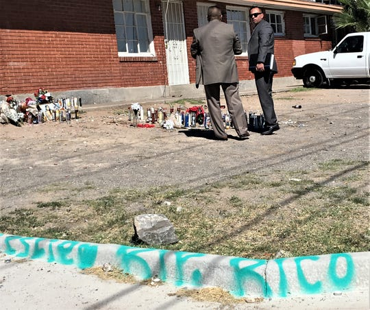 Police homicide detectives look at a memorial for three teens killed in a shooting on Lincoln Avenue in Central El Paso.