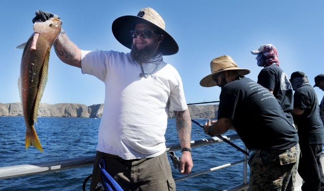 Chris Hightland of Ventura, a Navy veteran, shows off a fish he caught on a recent trip to Anacapa Island. The trip was organized by Anglers Anonymous, a group that takes veterans fishing so they can build friendships.
