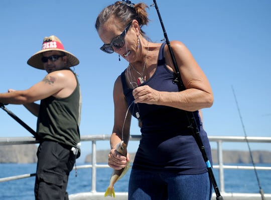 Liz Greco, a recreation therapist at the VA Long Beach Health Care System, catches a fish during a recent fishing trip with Anglers Anonymous near Anacapa Island. The group takes veterans fishing so they can build friendships.