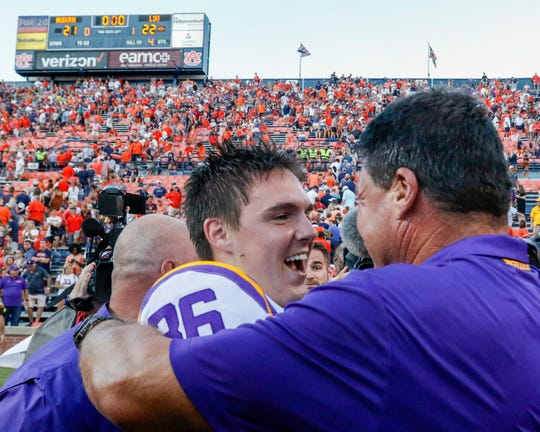 Newbury Park High graduate Cole Tracy is congratulated by LSU head coach Ed Orgeron after Tracy kicked the game-winning field goal against Auburn last Saturday.