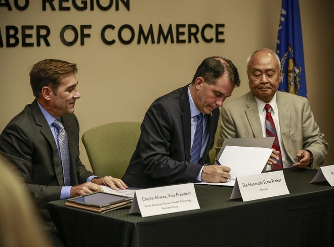 Governor Scott Walker, middle; along with Charlie Alvarez, vice president of North American Foxconn Health Technology Business Group, left; and Paul Hsu, founder of Hsu's Ginseng Enterprises; sign the letter of intent Tuesday, Sept. 18, 2018, at the Wausau Region Chamber of Commerce in Wausau, Wis. T'xer Zhon Kha/USA TODAY NETWORK-Wisconsin