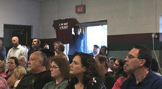 "A tenant of Stillwater Landing Mobile Home Community holds up a shirt reading ""I am not a blight"" at Monday night's Community Development Authority meeting in the village of Weston."