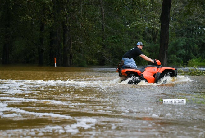 Jacob McPherson, 23, from Whiteville rides through the flooded intersection of Red HIll Road and Green Elkins Road completely cut off by flooding of the Red Hill Swamp near Whiteville, NC. on Sept. 17, 2018