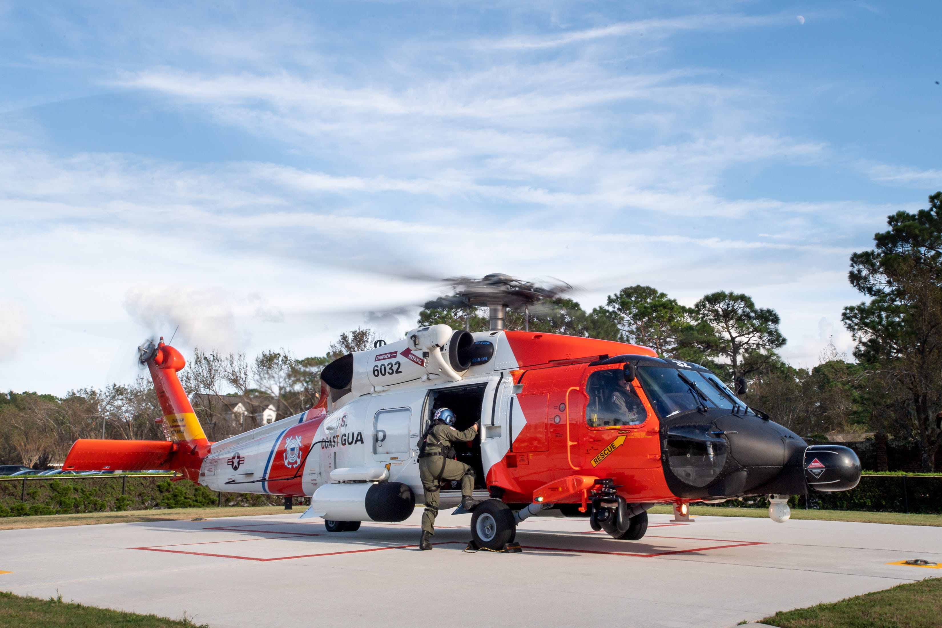 Coast Guard Flight Mechanic  Nick Gilkinson climbs into a MH-60T Jayhawk helicopter after dropping off a patient at the New Hanover Regional Medical Center in Wilmington, N.C., on Sept. 17, 2018.