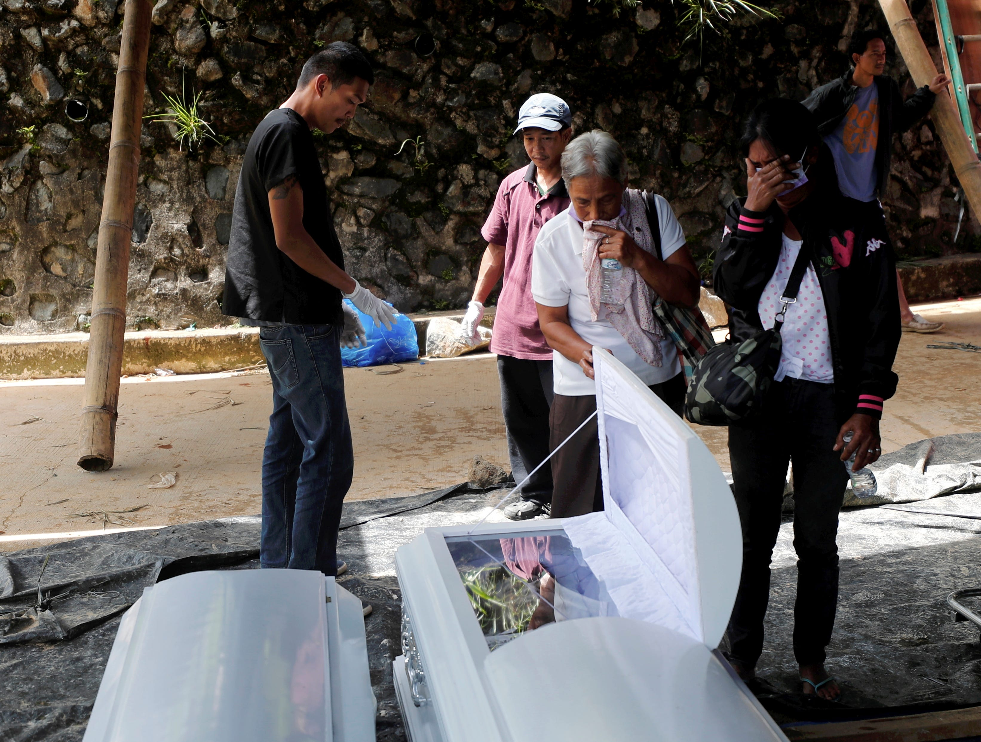 Filipino relatives of landslide victims cry in front of their coffins during rescue and retrieval operation for landslide victims caused by Typhoon Mangkhut in Ucab village, Itogon, Benguet Province, Philippines on Sept. 18, 2018.