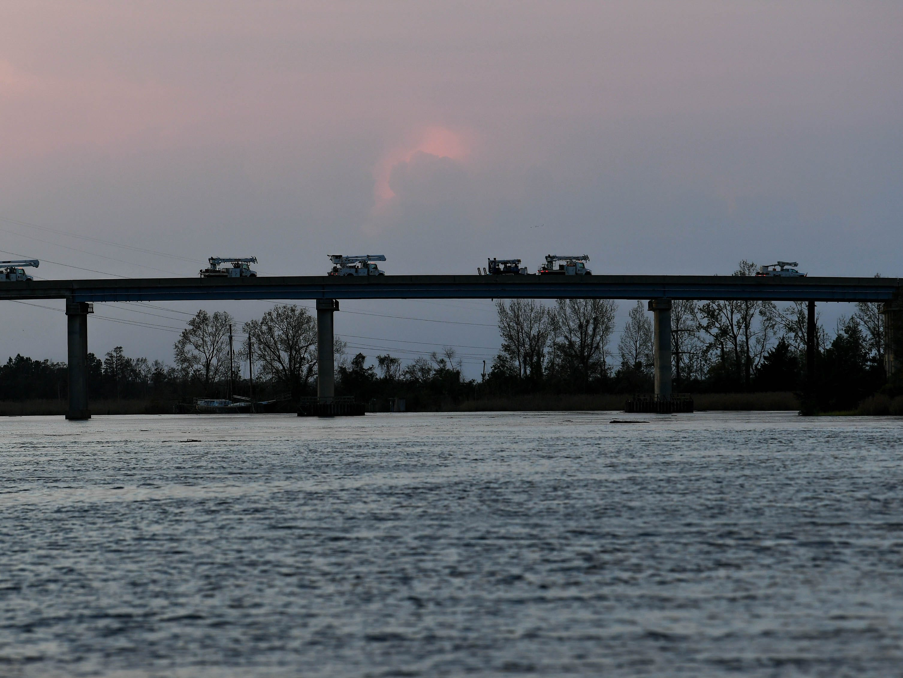 Utility crews move across a bridge on the opposite side of the Cape Fear River from Wilmington, NC Monday evening, Sept. 17, 2018. The Cape Fear River is expected to crest on Tuesday, September 18.