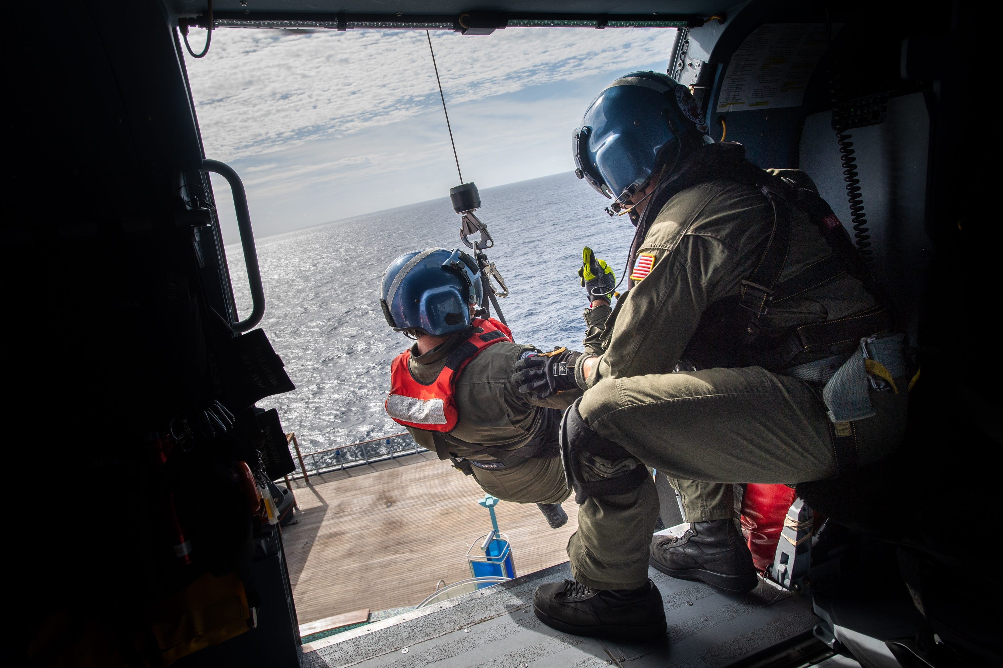 Coast Guard Flight Mechanic Nick Gilkinson, right, lowers rescue swimmer Scott Garren to retrieve a patient from the Carnival Pride on Sept. 17, 2018.