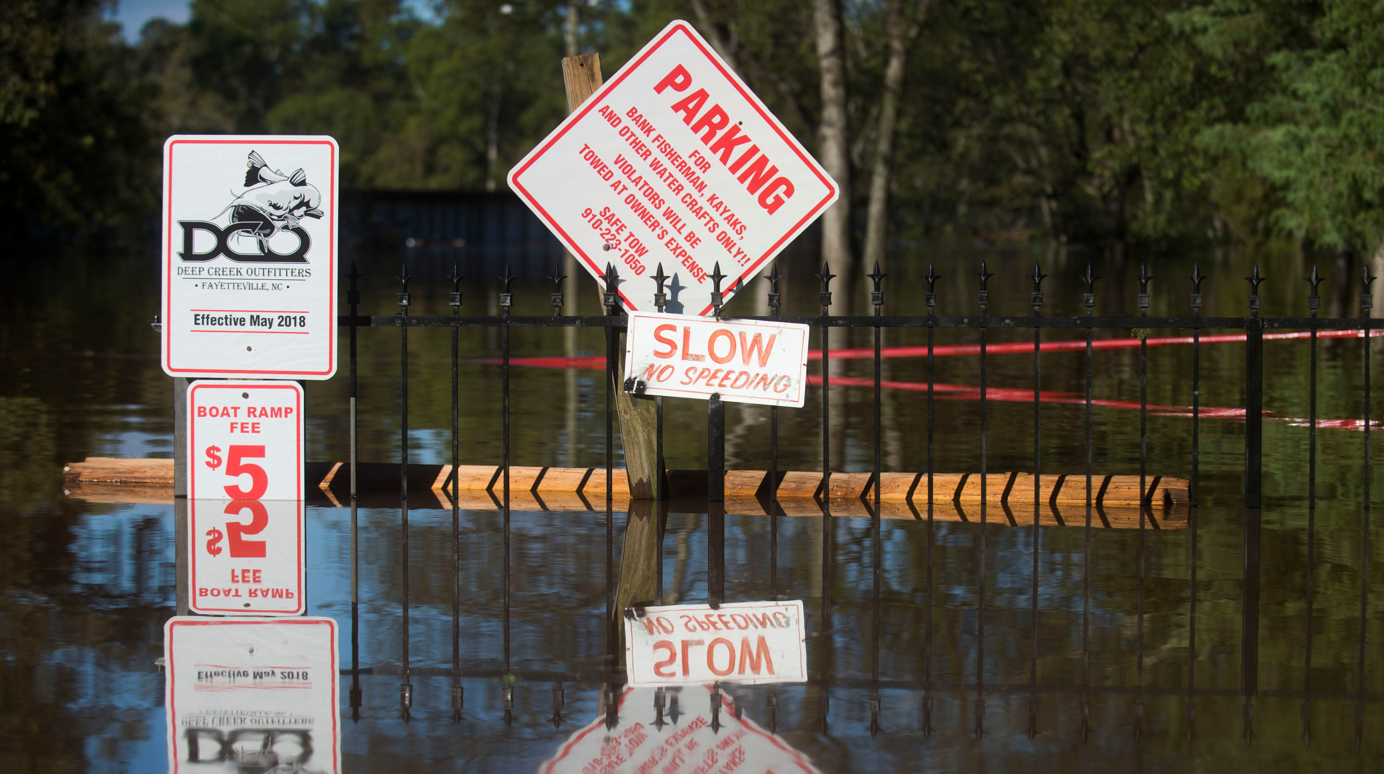Signs peak above the flooded Cape Fear River outside in Fayetteville, N.C. Tuesday, Sept.18, 2018.