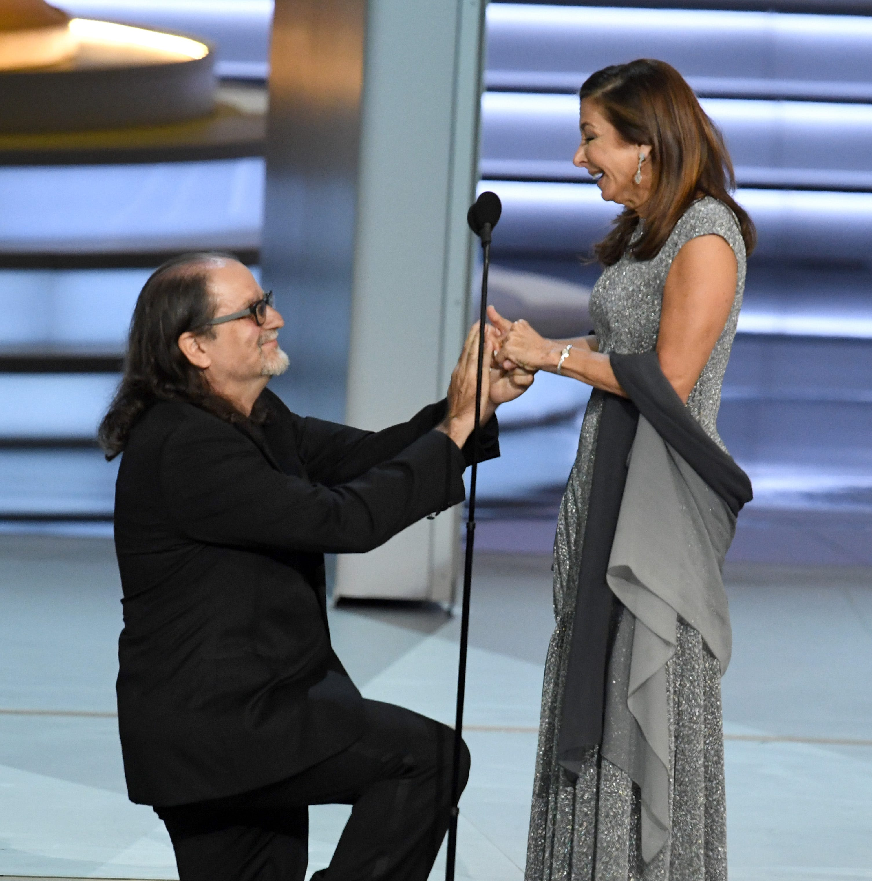 Glenn Weiss  (L), winner of the Outstanding Directing for a Variety Special award for 'The Oscars,' proposes marriage to Jan Svendsen onstage during the 70th Emmy Awards.