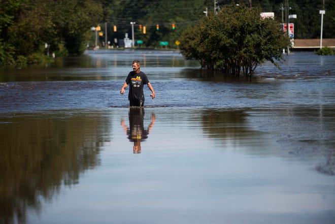 Spring Lake resident Patrick Wolvin wades through water from the flooded Little River, to buy his wife and neighbors cigarettes, in Spring Lake on the outskirts of Fayetteville, N.C., Tuesday, Sept. 18, 2018.