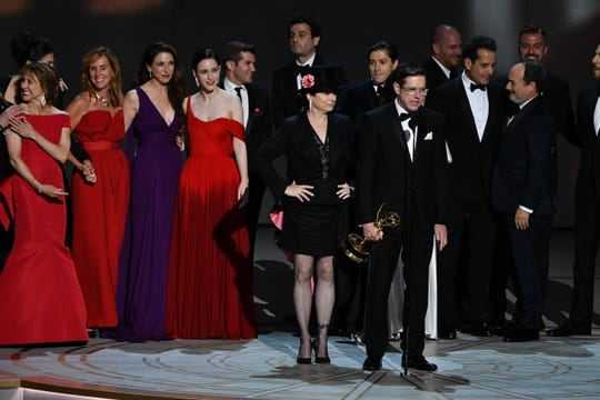 """Writers/directors Amy Sherman-Palladino and Daniel Palladino (center) took to the stage with their cast and crew to celebrate the night's fifth win for """"The Marvelous Mrs. Maisel,"""" which won the best comedy series Emmy."""