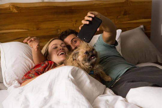 """Abby (Olivia Wilde) and Will (Oscar Isaac) pose with their pooch for a selfie in the ensemble drama """"Life Itself."""""""
