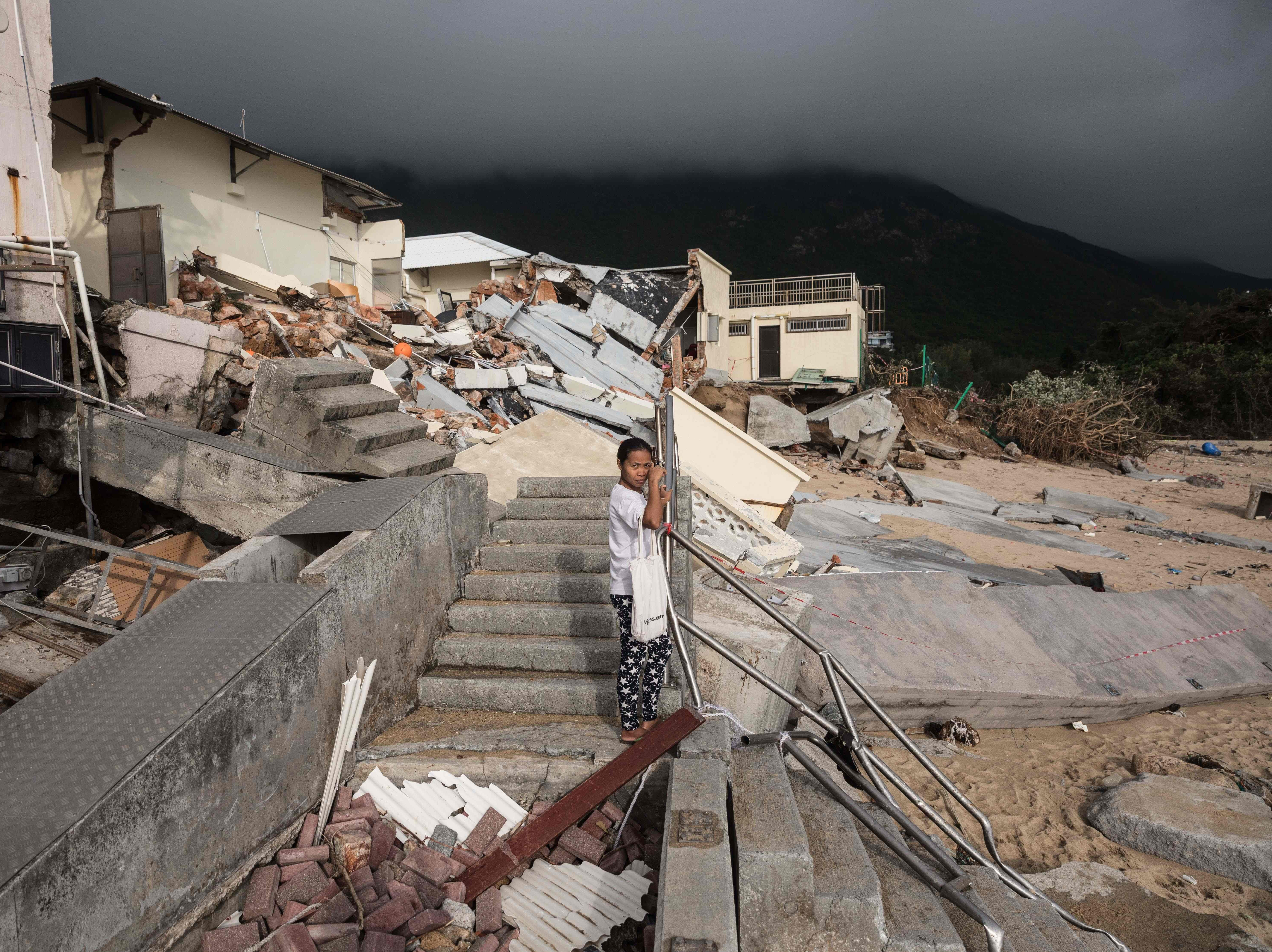 A woman stands before a collapsed building of a school next to a beach in the aftermath of Typhoon Mangkhut in the coastal village of Shek O in Hong Kong on Sept. 18, 2018. Hong Kong was still struggling to get back on its feet, with a massive clean-up operation to clear broken trees, repair torn-up roads and fix damaged power lines. The violent typhoon killed four in China's southern province of Guangdong and the toll climbed on Tuesday to 74 on the Philippines' northern Luzon island according to police, with that number expected to rise.