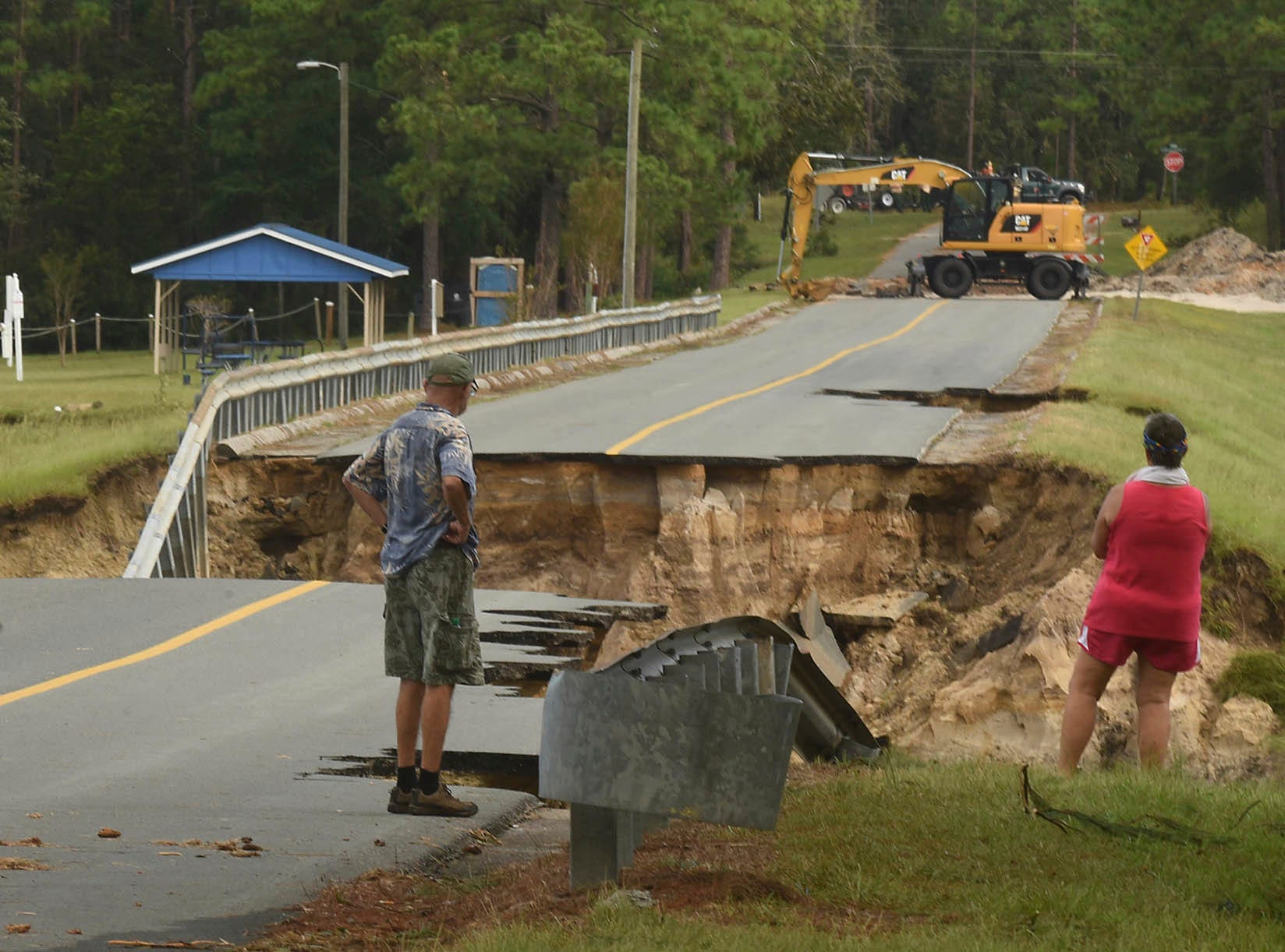 Mary and Phil Pongonis look at the damaged roadway from Hurricane Florence in Boiling Spring Lakes, N.C. Tuesday Sept. 18, 2018.