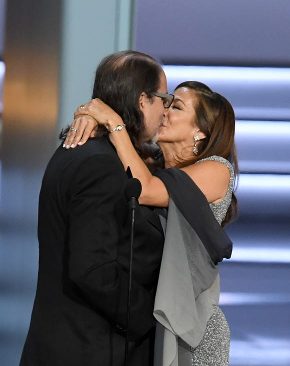 Glenn Weiss  (L), winner of the Outstanding Directing for a Variety Special award for 'The Oscars,' and Jan Svendsen kiss after getting engaged onstage during the 70th Emmy Awards.