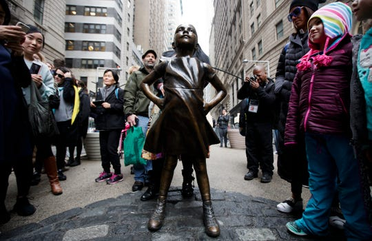 People look at the 'Fearless Girl' girl statue in Lower Manhattan. The statue was installed by a Wall Street financial firm in conjunction with the 2017 International Women's Day as way to call attention to a lack of diversity and the gender pay gap.