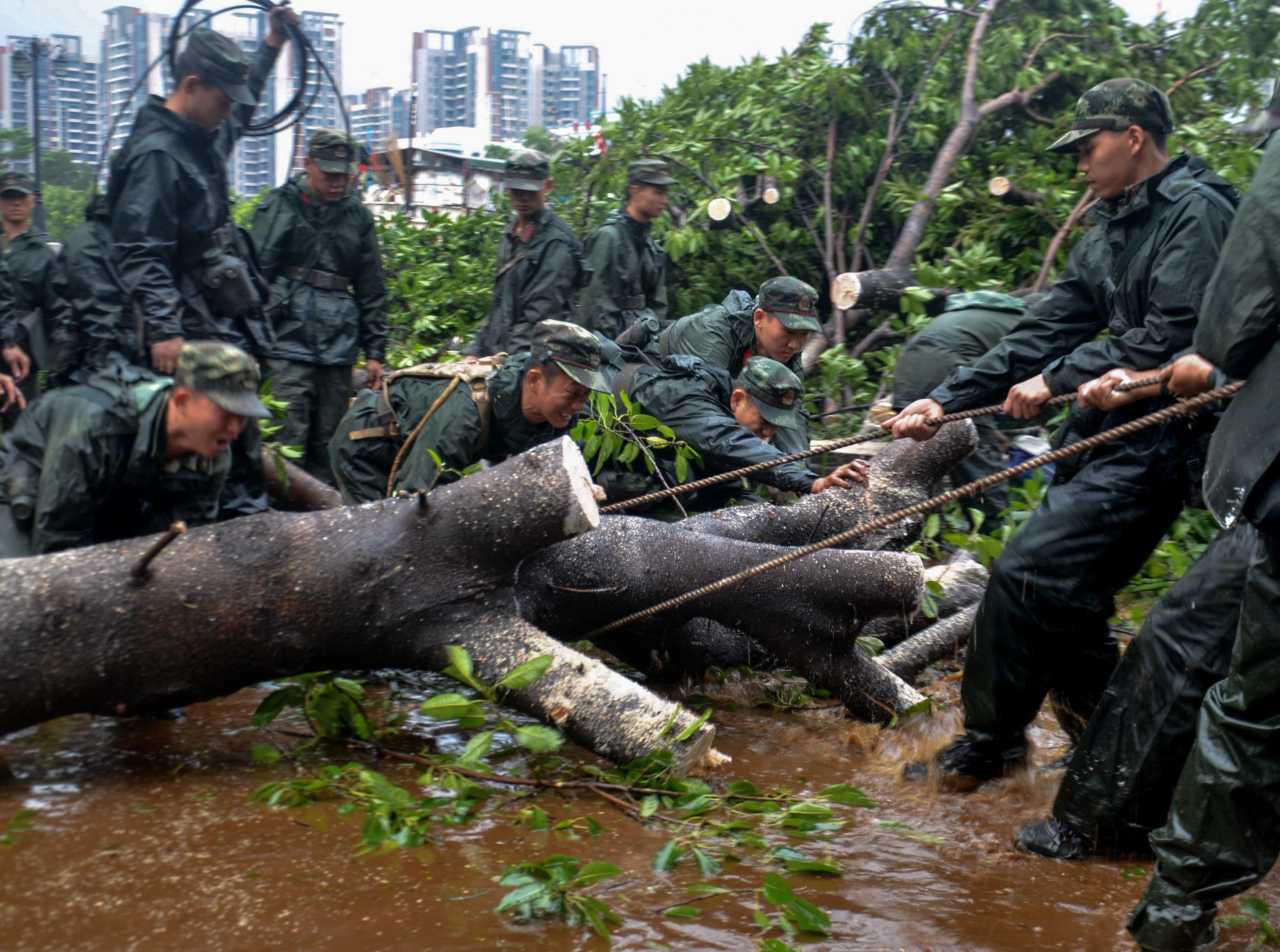 This photo taken on Sept. 17, 2018 shows Chinese paramilitary police officers clearing branches on a road, a day after Typhoon Mangkhut hit in Zhongshan, in China's southern Guangdong province.