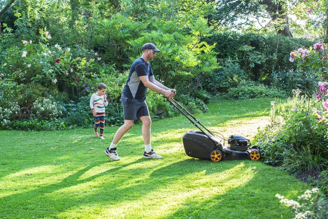 Stock photo of a man mowing the lawn