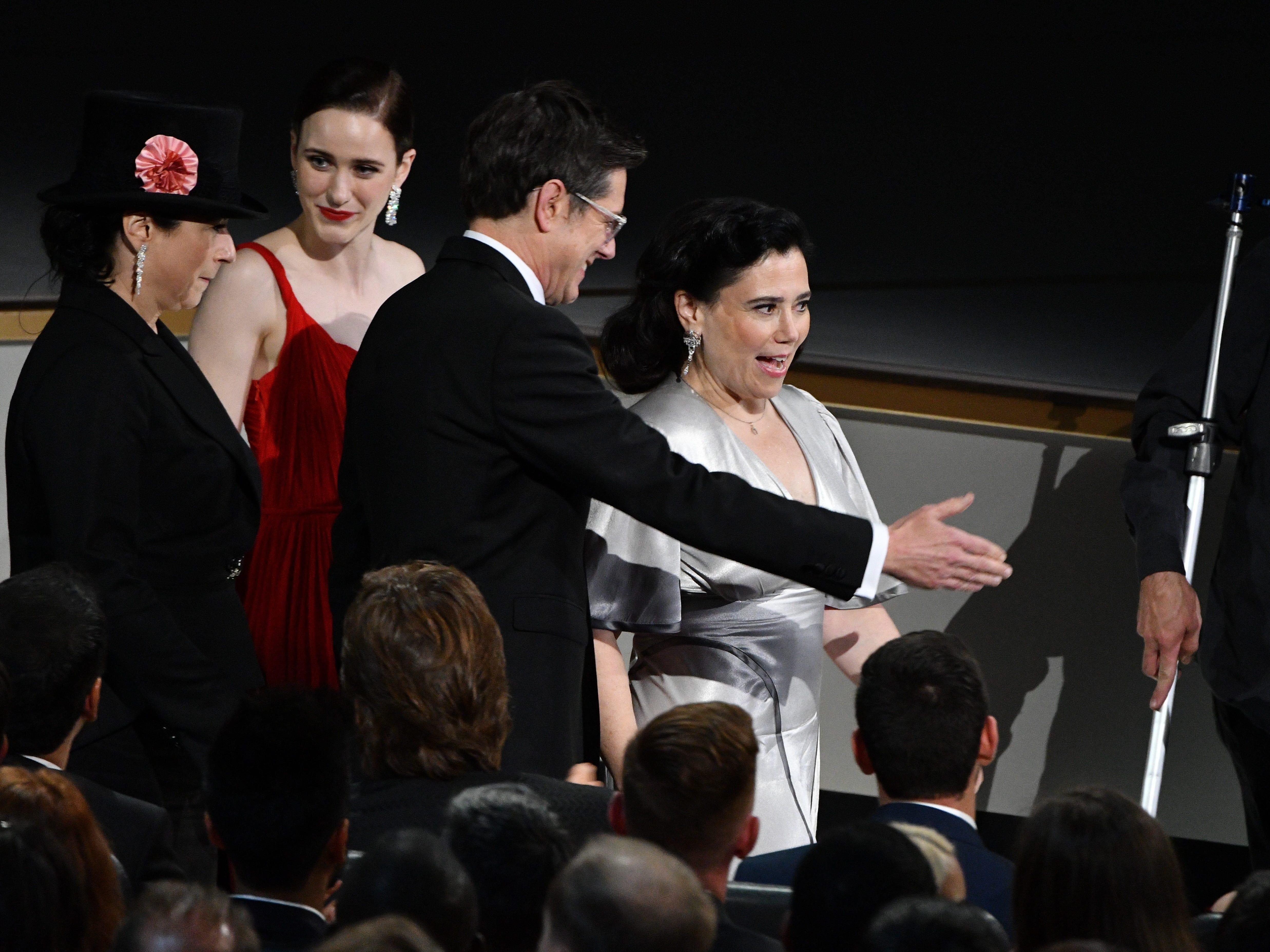 Amy Sherman-Palladino, Rachel Brosnahan, Daniel Palladino and Alex Borstein walk towards the stage to accept the award for outstanding comedy series.
