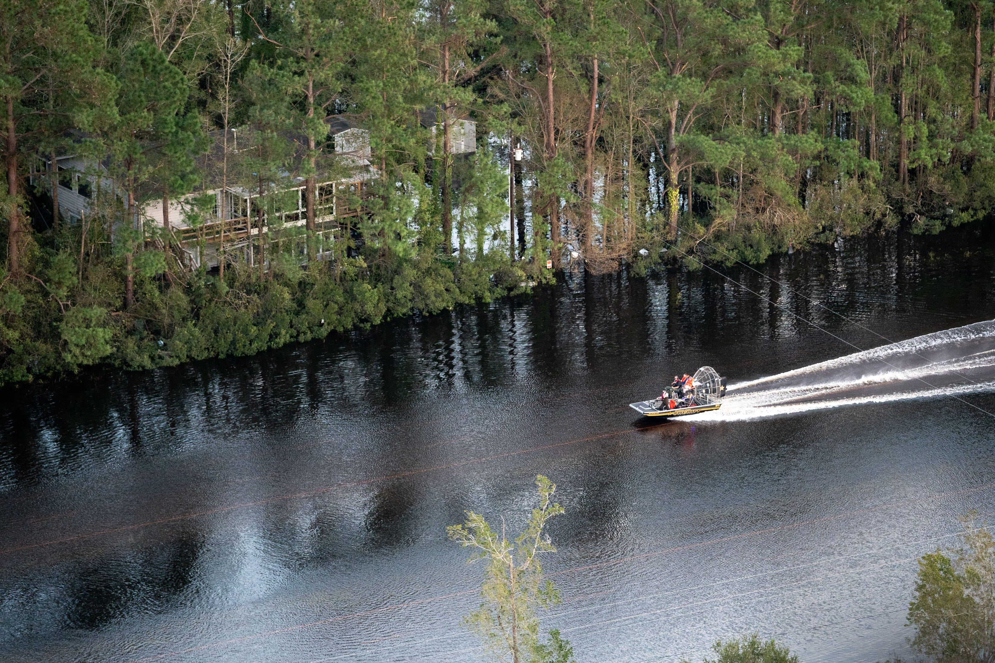 A boat speeds down the flooded U.S. 17, as seen from a Coast Guard helicopter, in Brunswick County, N.C., on Sept. 17, 2018.