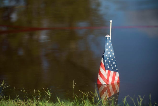 A flag marks where the Cape Fear River rose to during Hurricane Matthew in 2016, outside of Deep Creek Outfitters in Fayetteville, N.C. Tuesday, Sept.18, 2018.  Tuesday morning the river stands inches below 60 feet. The flood stage for the river is 35 feet.