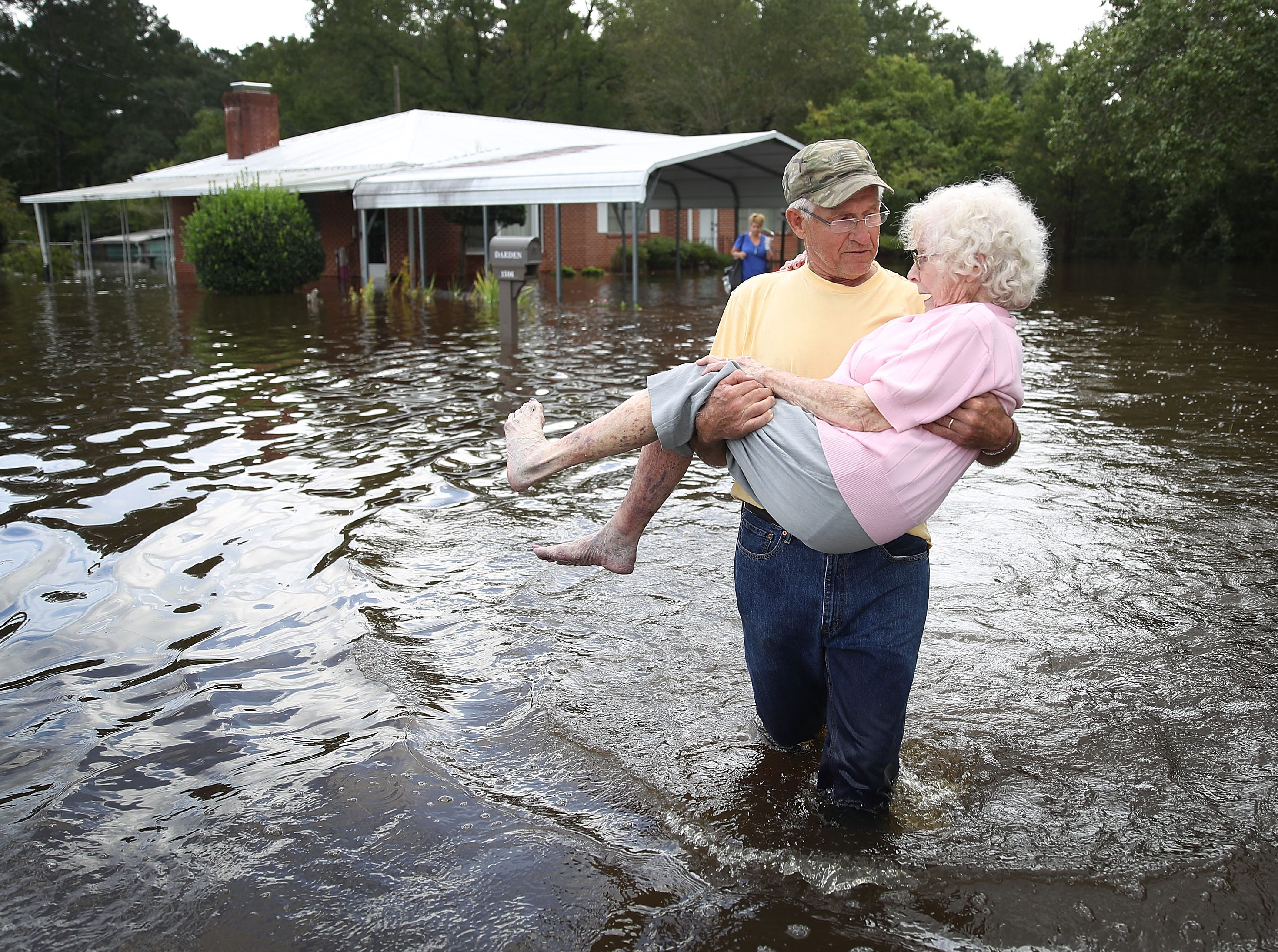 Bob Richling carries Iris Darden as water from the Little River starts to seep into her home on Sept. 17, 2018 in Spring Lake, North Carolina. Flood waters from the cresting rivers inundated the area after the passing of Hurricane Florence.