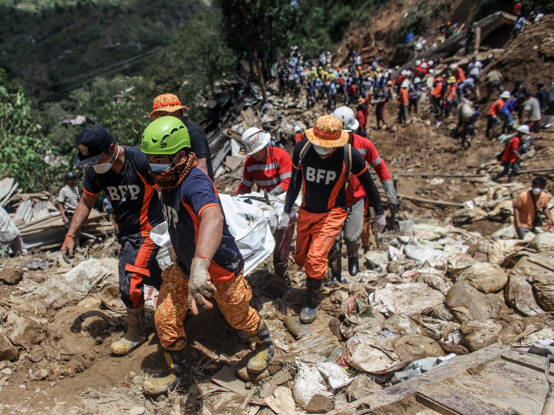 Filipino rescuers carry a body of a person inside a body bag at the site where people were believed to have been buried by a landslide on Sept. 18, 2018 in in Itogon, Benguet province, Philippines. At least 36 people are feared to be buried by a landslide in the mining town of Itogon, in Benghuet province, after Super Typhoon Mangkhut triggered a massive landslide in northern Philippines which destroyed hundreds of homes and killed over 60 people. The storm slammed into the main Philippine island of Luzon over the weekend and continued its path through Hong Kong and Southern China, killing four people in the province of Guangdong as 2.5 million people were evacuated in Guangdong and on Hainan island.
